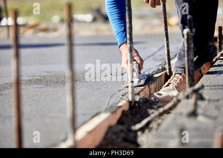 A mason using a concrete trowel to finish a newly poured concrete slab with shallow depth of field - Stock Photo