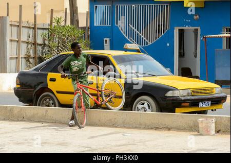 DAKAR, SENEGAL - APR 27, 2017: Unidentified Senegalese little boy holds a bicycle in Dakar, the capital of Senegal - Stock Photo