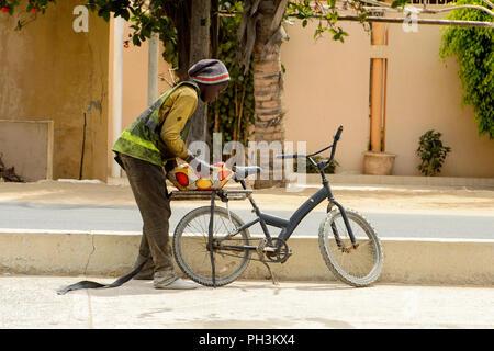 DAKAR, SENEGAL - APR 27, 2017: Unidentified Senegalese little boy binds a pillow to the bicycle in Dakar, the capital of Senegal - Stock Photo