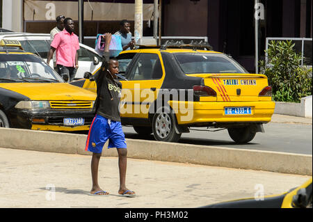 DAKAR, SENEGAL - APR 27, 2017: Unidentified Senegalese little boy carries a basin on his head in Dakar, the capital of Senegal - Stock Photo