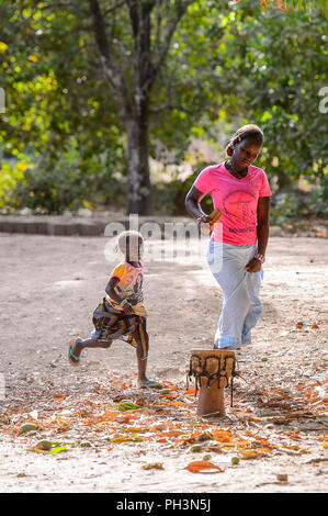 OUSSOUYE, SENEGAL - APR 30, 2017: Unidentified Senegalese  woman in pink shirt and skirt walks with a little girl with brads nearby in the Sacred Fore - Stock Photo