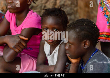 OUSSOUYE, SENEGAL - APR 30, 2017: Unidentified Senegalese little girl with braids looks ahead in the Sacred Forest near Kaguit village - Stock Photo