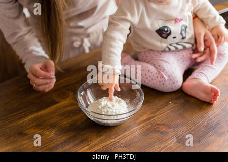 Happy loveling family preparing dough together. Mother and daughter having fun in the kitchen. Homemade food and little helper. - Stock Photo