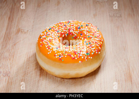 Single delicious donut on wood - Stock Photo