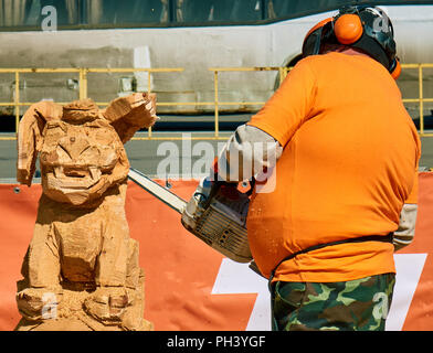 Experienced carpenter making a big wooden dog sculpture with a chainsaw during a local competition, almost finished - Stock Photo