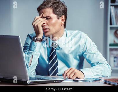 Young office man with pain in his head or an eye. Photo of man suffering from stress or a headache grimacing in pain. Business concept - Stock Photo