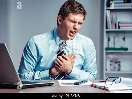 Office manager having heart attack. Photo of young man holding hand on painful chest in the workplace. Medical concept. - Stock Photo