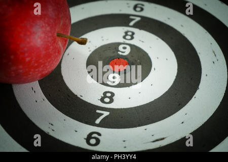 Conceptual image of a target board with red bulls eye center and a fresh juicy red apple placed on top in a close up view - Stock Photo
