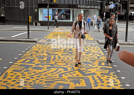 Kishimoto geometric artwork & young women walking across road yellow pedestrian crossing near Barbican station in the City of London UK KATHY DEWITT - Stock Photo