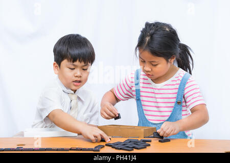 Little boy and beautiful girl playing domeno in wooden table on white background, - Stock Photo