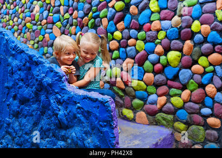 Two happy kids have fun together sitting outside home on colorful stone steps. Playful girl hug laughing younger brother. Travel lifestyle, walking ci - Stock Photo