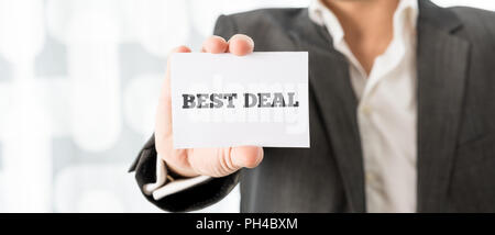 Businessman holding a small white business card with the words - Best Deal - in a promotional concept of the best offer, close up of his hand. - Stock Photo