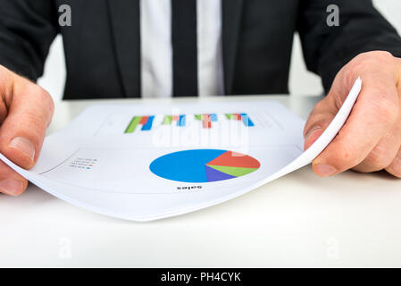 Close up of a businessman analysing a set of bar and pie graphs as he sits at his white desk. - Stock Photo