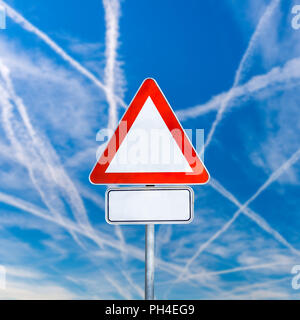 Blank white triangular traffic warning sign on a signpost against a sunny blue sky with crisis-crossing contrails from jetliners with copyspace for yo - Stock Photo