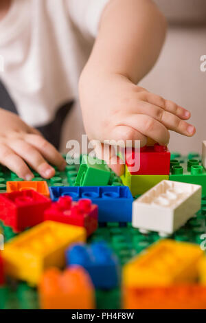 Close up of child's hands playing with colorful plastic bricks at the table. Toddler having fun and building out of bright constructor bricks. Early l - Stock Photo