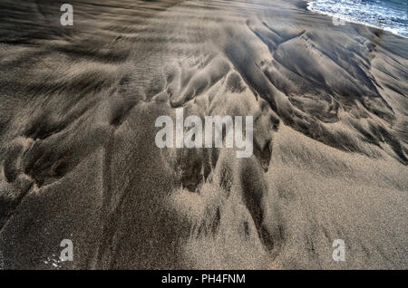 Water edge and beautiful pattern made by waves of Atlantic ocean on real wet black volcanic sand beach at Madeira island, Portugal. Textured backgroun - Stock Photo