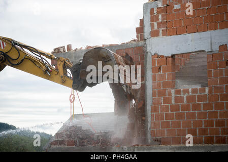 View of the hydraulic arm and bucket of a large heavy duty backhoe demolishing a brick house breaking down the exterior wall for removal. - Stock Photo