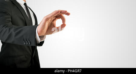 Close up Businessman Showing Conceptual OK Hand Sign on an Abstract Grey Background, Emphasizing Copy Space. - Stock Photo