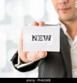Businessman holding up a white card with word New on it. Conceptual of consumerism, retail and marketing. - Stock Photo