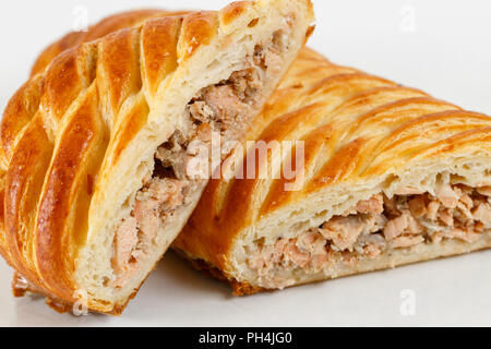 Tasty puff pastry dessert cut in half . Delicious pastries with minced fish on light background. - Stock Photo