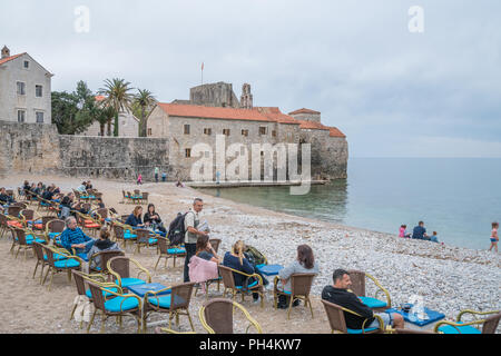 Budva, Montenegro - April 2018 : Tourists sitting on  chairs on the beach outside a cafe, enjoying coffee, refreshments and desserts - Stock Photo