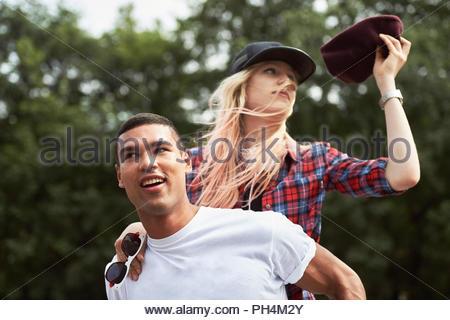 Teenage boy giving teenage girl piggyback ride - Stock Photo