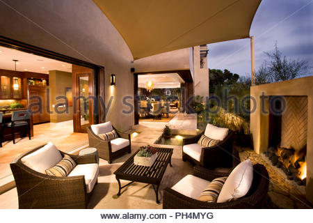Outdoor chairs by fireplace on patio - Stock Photo