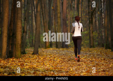 Image from back of young sports girl in running through forest - Stock Photo