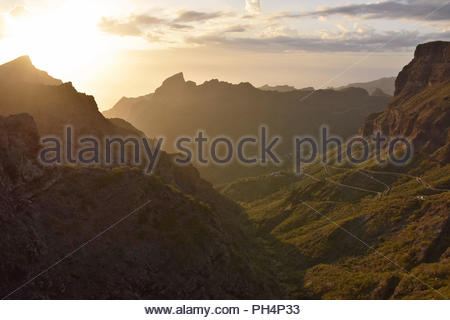 Masca Valley in the northwest of Tenerife Canary Islands Spain. Sun setting behind volcanic peaks of Teno Massif. Scenic view from Mirador de Cherfe. - Stock Photo