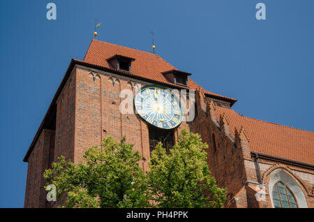 Big outside ancient clock on the Old Town Hall in Torun, Poland. Low angle view. Summer sunny day - Stock Photo