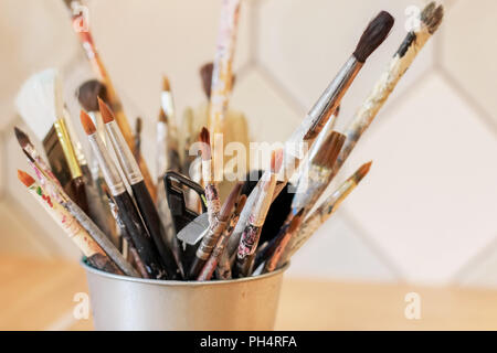 Different brushes of the artist in a metal bucket, selective focus - Stock Photo