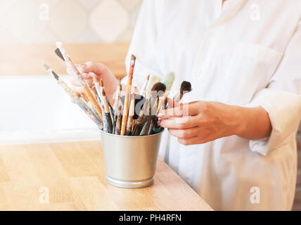 Different brushes in metal bucket with artist hands, selective focus - Stock Photo