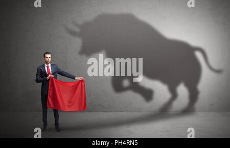Businessman standing with red cloth in his hand and big bull shadow on the wall  - Stock Photo