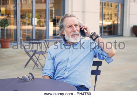 Senior man on phone call at table - Stock Photo