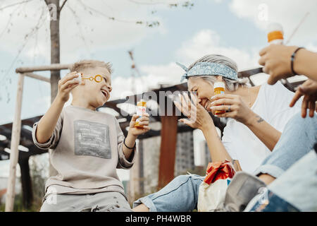 Close up of family blowing bubbles outdoors in the park. - Stock Photo