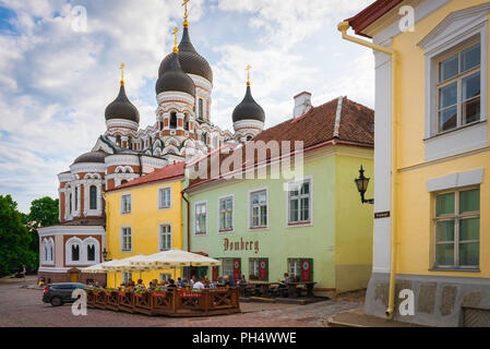 View of people eating at a restaurant terrace on Toompea Hill with the Alexander Nevsky Orthodox Cathedral at the end of the street, Tallinn, Estonia. - Stock Photo