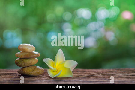 Balance Zen stones and yellow plumeria on wood with green bokeh background. Zen and Spa concept. - Stock Photo