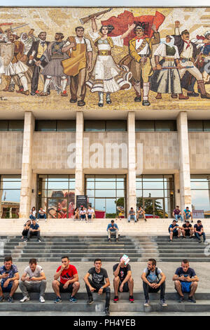 Young people relaxing on the steps of the National Historical Museum, below its, communist era, Mosaic mural, in Skanderbeg Square, Tirana, Albania, - Stock Photo