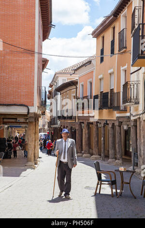 Old man with walking stick walking through the Spanish medieval walled town of Uruena known as the town of books Valladolid Castille y Leon Spain - Stock Photo