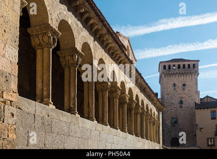 The Romanesque, arcaded portico  of San Martin church, looking towards the Torreón de Lozoya  in the Plaza Medina del Campo, Segovia, Spain - Stock Photo