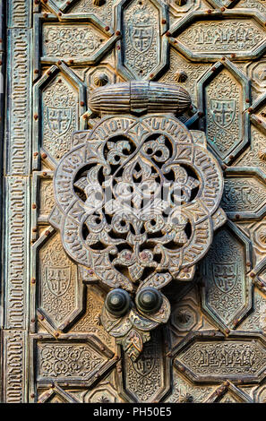 A door knocker on the ornate, bronze, Puerta del Perdon, door of forgivness,  of  the Great Mosque, La Mezquita, in Cordoba, Spain - Stock Photo