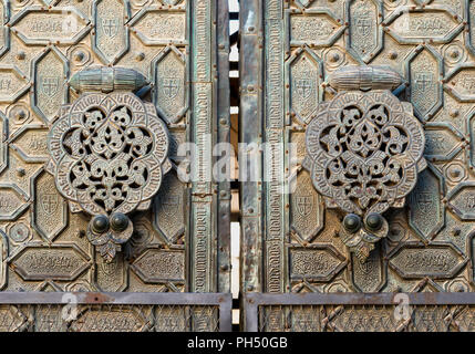 Door knockers on the ornate, bronze, Puerta del Perdon, door of forgivness,  of  the Great Mosque, La Mezquita, in Cordoba, Spain - Stock Photo