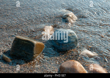 A group of pebbles by the sea shore partly immersed in sea water