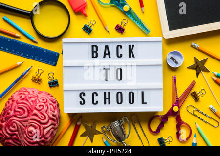 Back to school lightbox message on a bright yellow background - Stock Photo