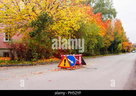 road sign road repair on a closed road section in the city on sunny autumn day - Stock Photo