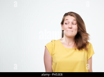 Headshot of cunning beautiful woman in yellow t-shirt looking aside indenting to realize tricky plan. - Stock Photo