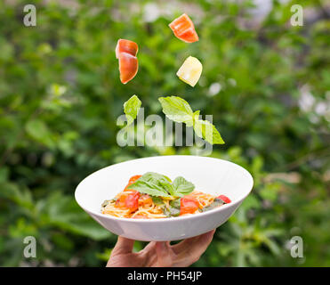 Plate of spaghetti marinara with fresh tomatoes and basil suspended in the air above it. - Stock Photo