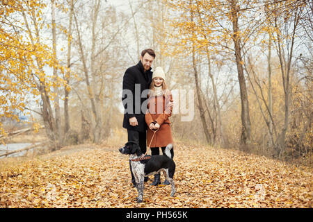 Couple in love on Valentine's day walking in the Park with the dog. The love and tenderness between a man and a woman. Valentine's day is a holiday of - Stock Photo