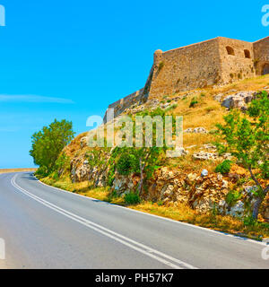 Road turn and the fortezza of Rethymno, Crete, Greece - Stock Photo