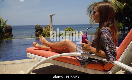 Beautiful young girl with glass of cocktail relaxing near swimming pool. Girl in sunglasses with cocktail in seafront near the bassin amongst the palm trees on the background of the sea. Travel, vacation concept. - Stock Photo